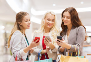 women with smartphones and shopping bags in mall